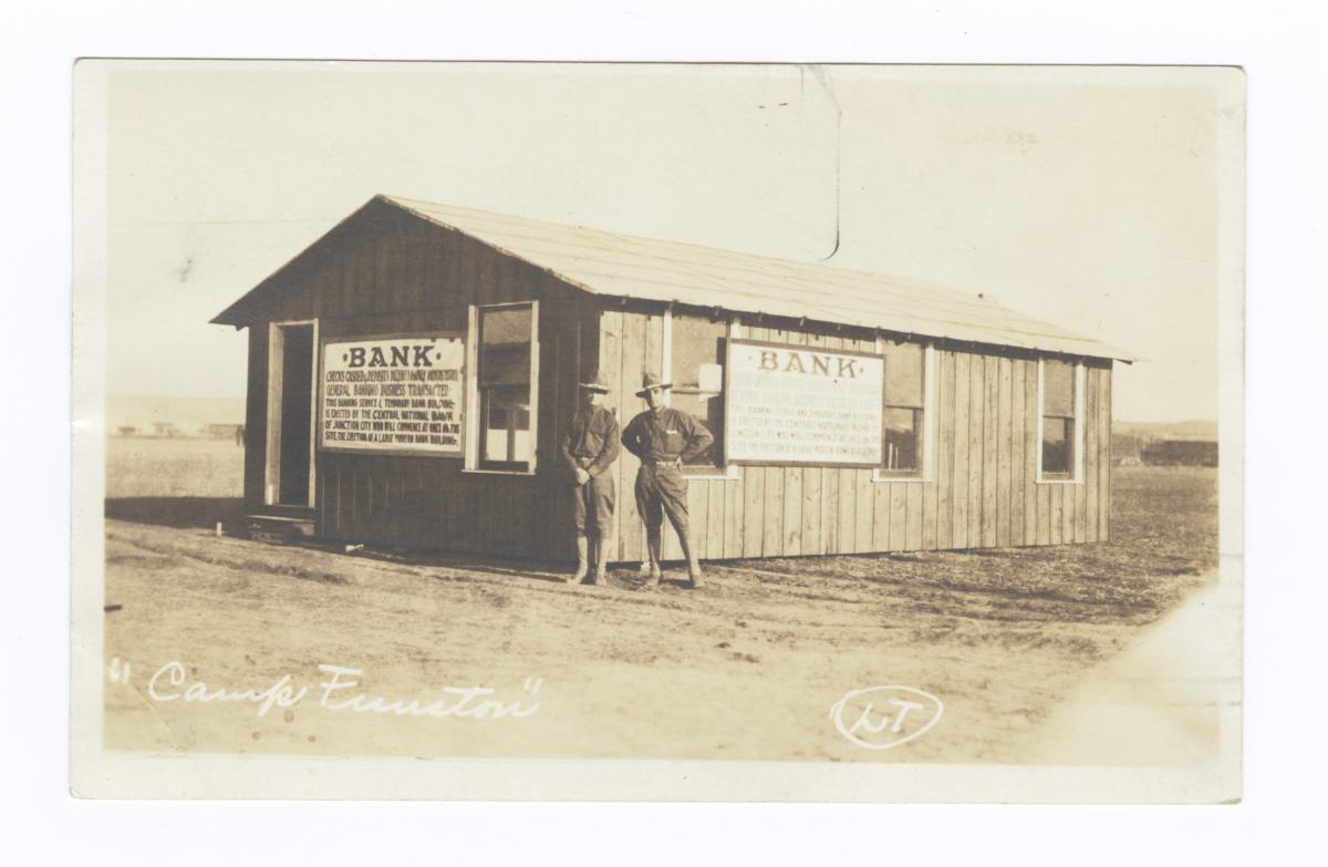Two Men in Uniform in front of Bank Building, Camp Function