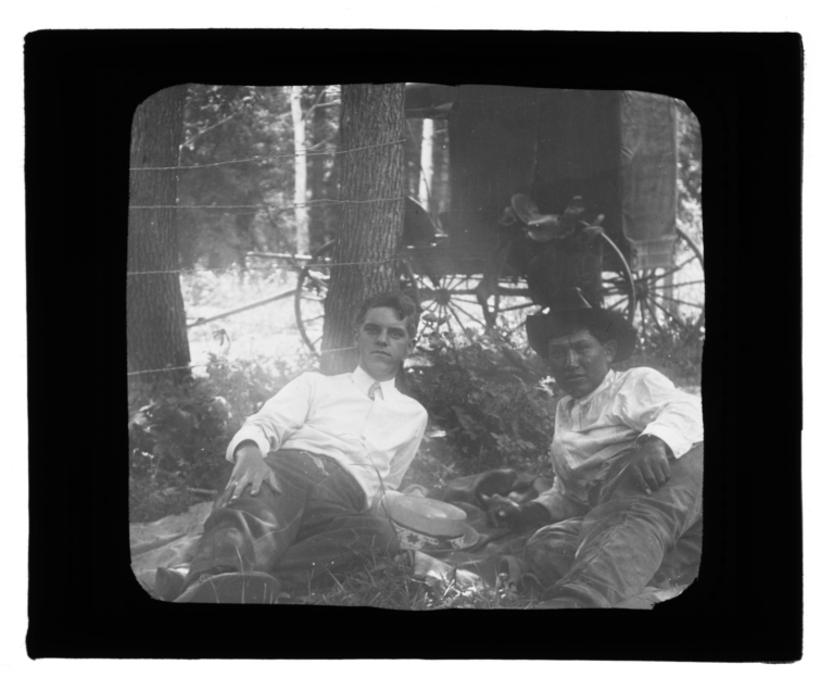 Two Men Lying next to a Wire Fence with a Carriage in the Background