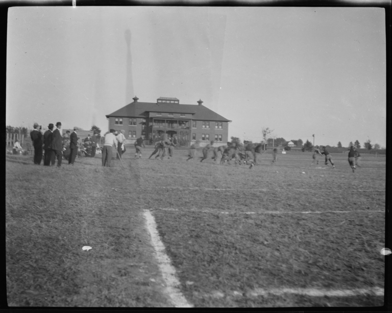 Football Game with Spectators Standing around the Field's Edge, Haskell Institute, Lawrence, Kansas