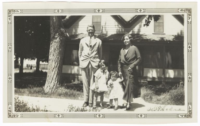 G.E.E. Lindquist with Woman and Two Children Posing in front of a House