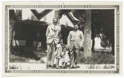 Two Men with Two Children Posing in front of a House