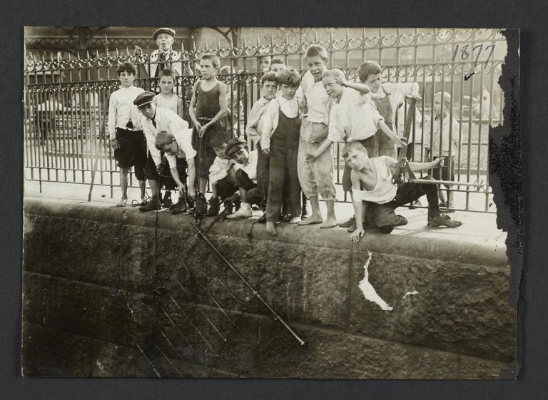Boys Against Iron Fence