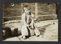 Boy Sitting on Paving Stone