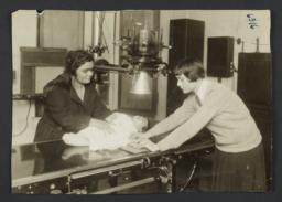 Mulberry Health Center Album -- Two Women Holding Baby on Examining Table