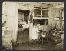 Little Girl Near Stove, Family in Next Room