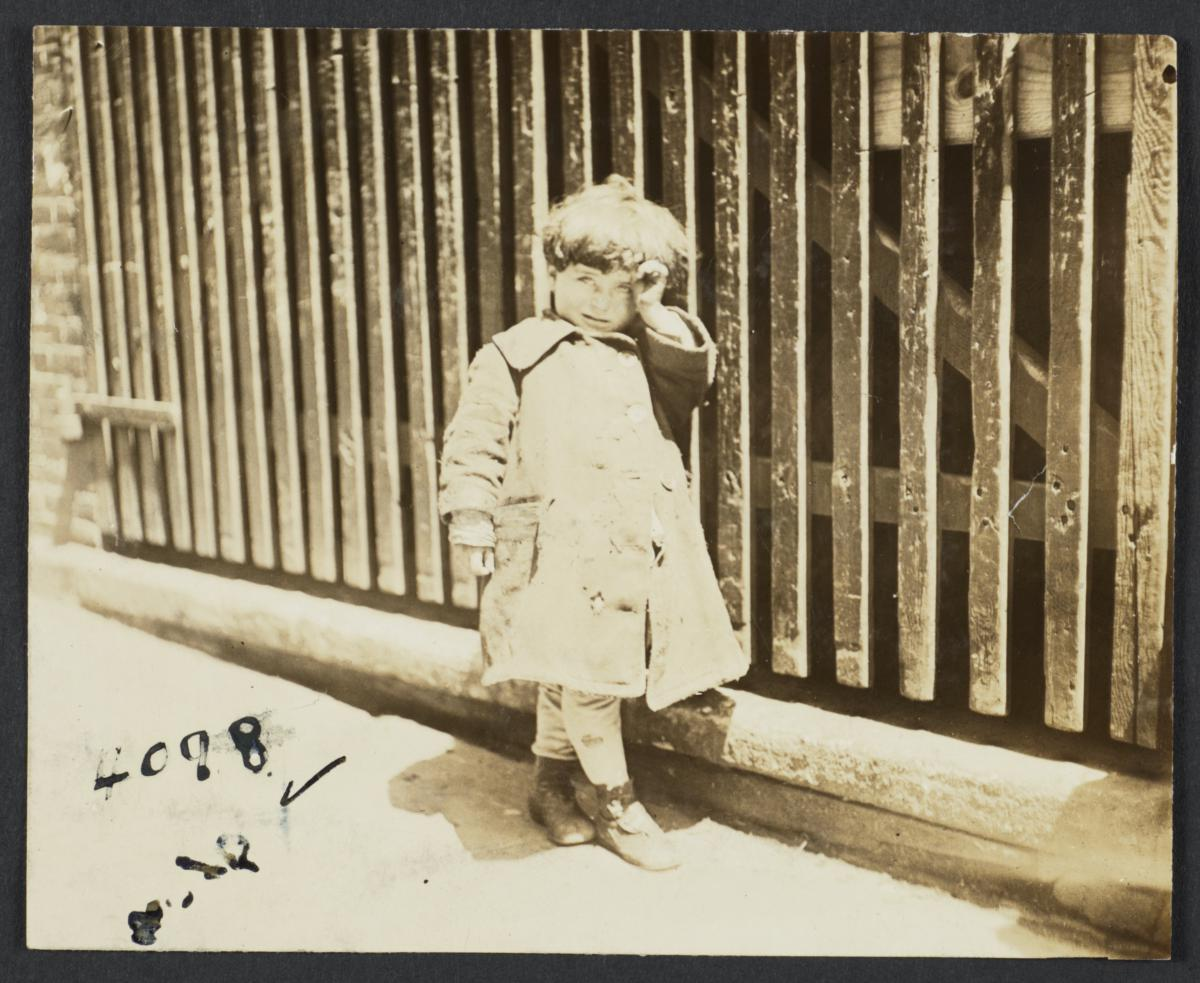 Child Beside a Wooden Fence