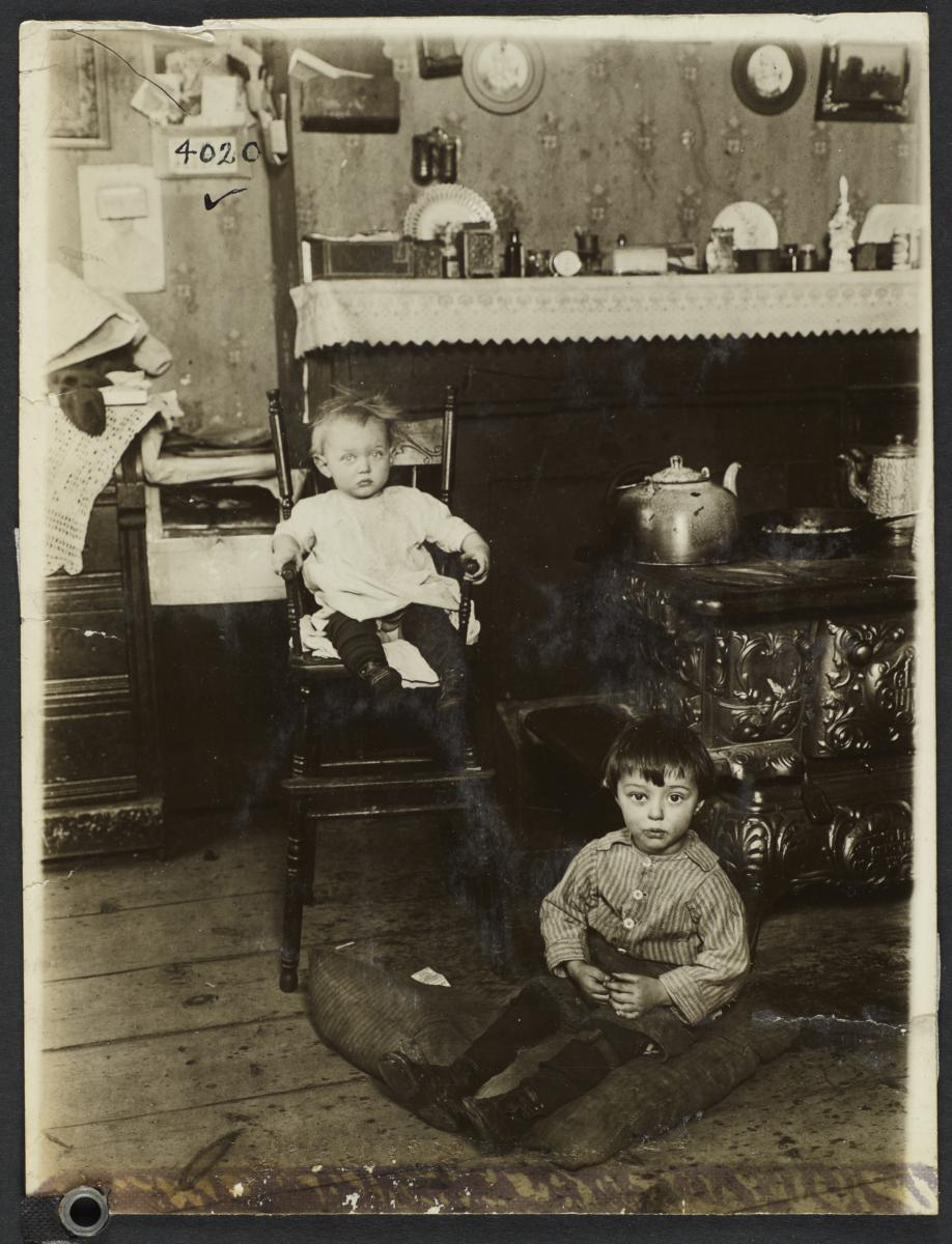 Baby in High Chair and Child on Floor