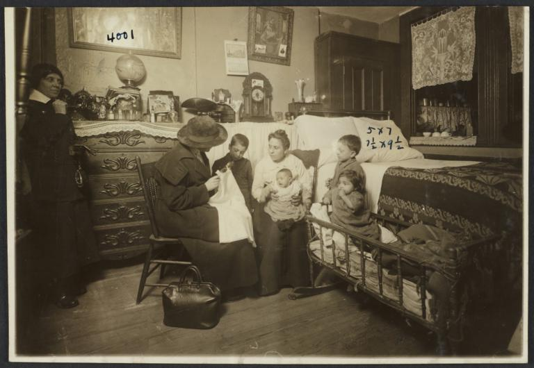 Mulberry Health Center Album -- Woman Showing Clothing to Family