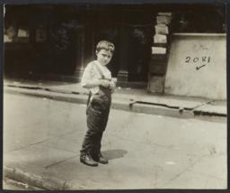 Boy in Overalls on Sidewalk