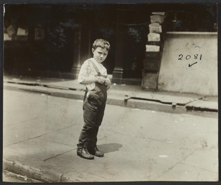 Boy in Overalls on Sidewalk