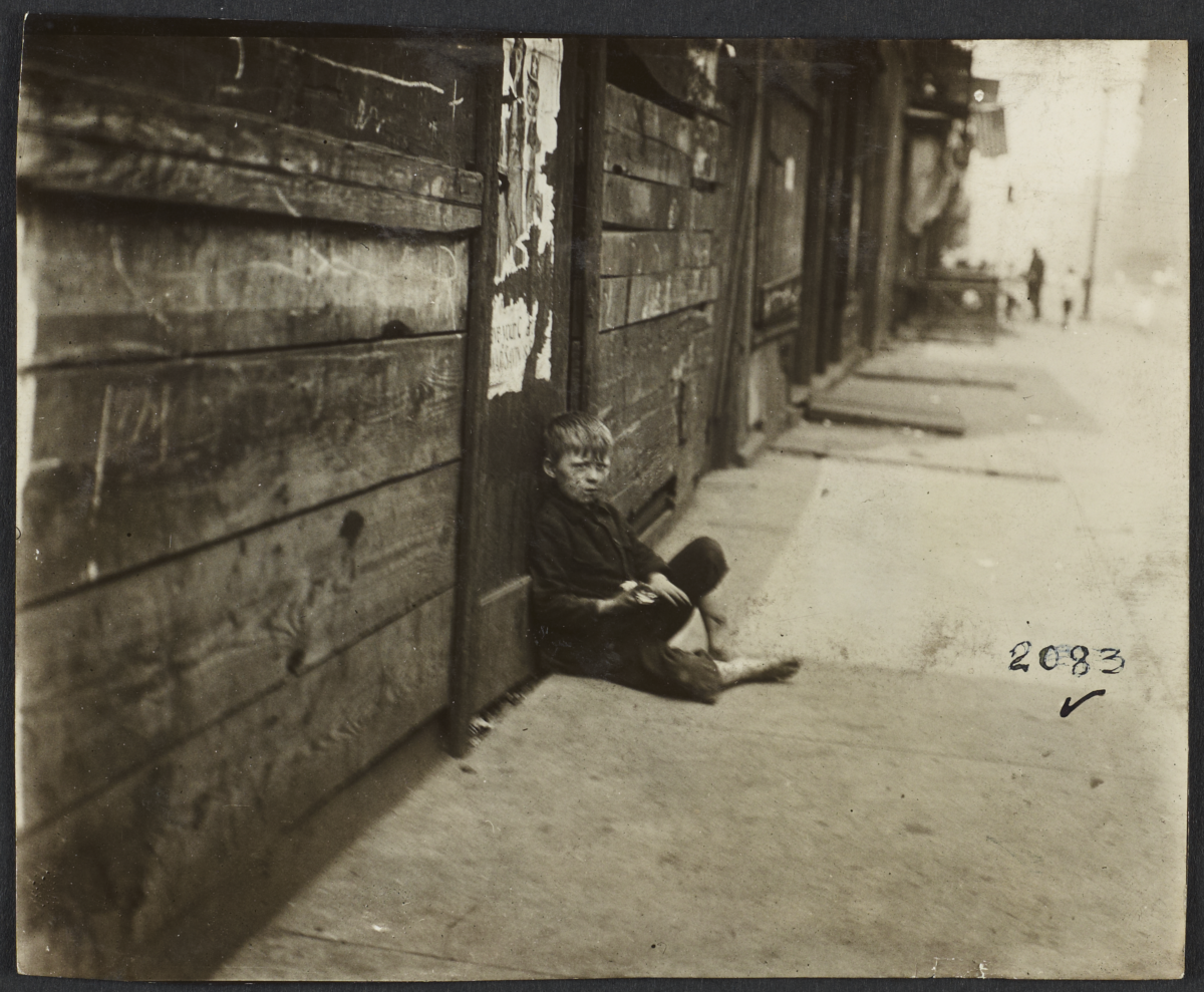 Boy Sitting on Sidewalk