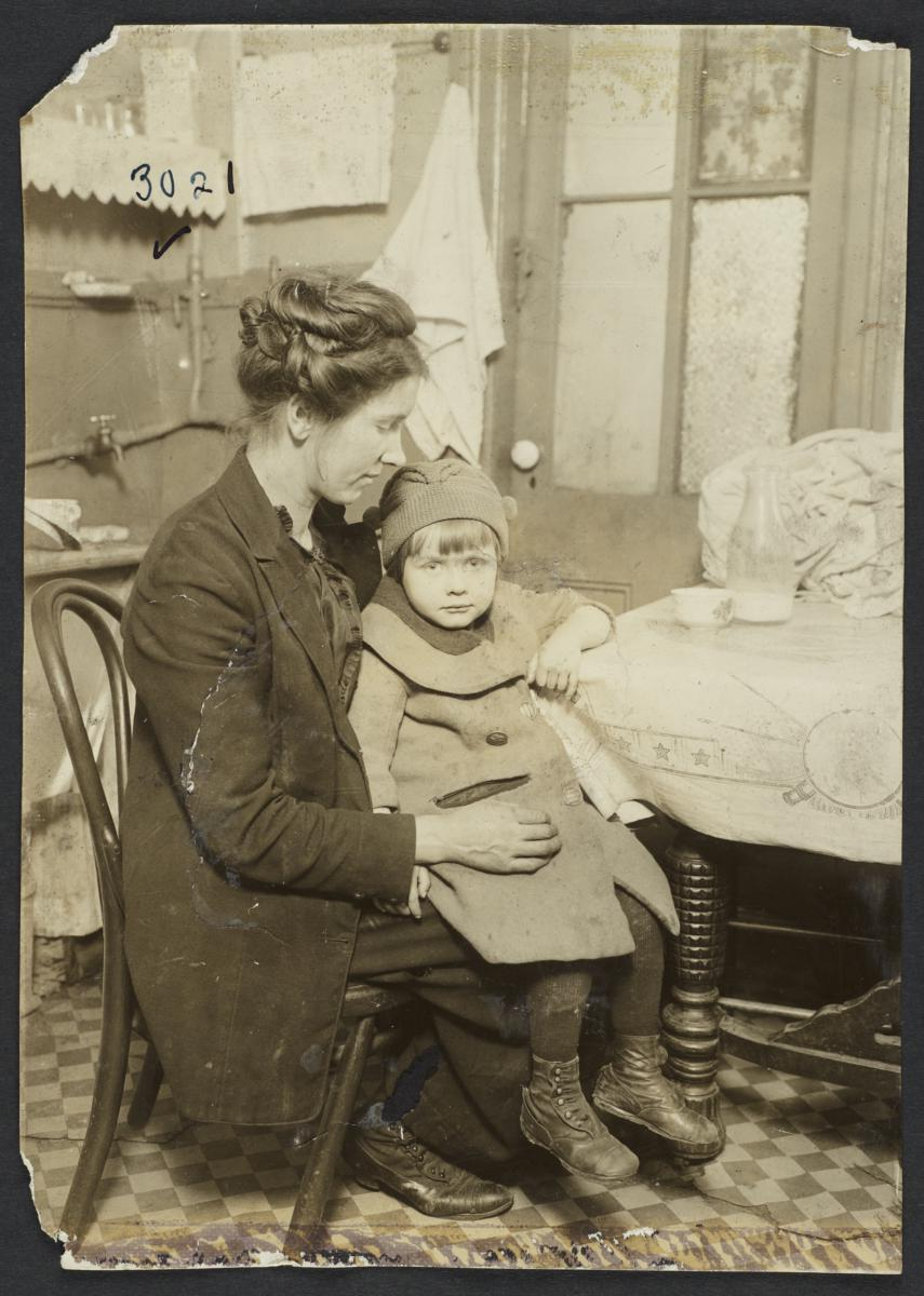 Woman Holding Child Near Table