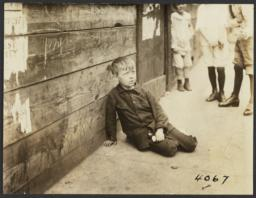 Boy Sitting on Sidewalk near Wooden Fence