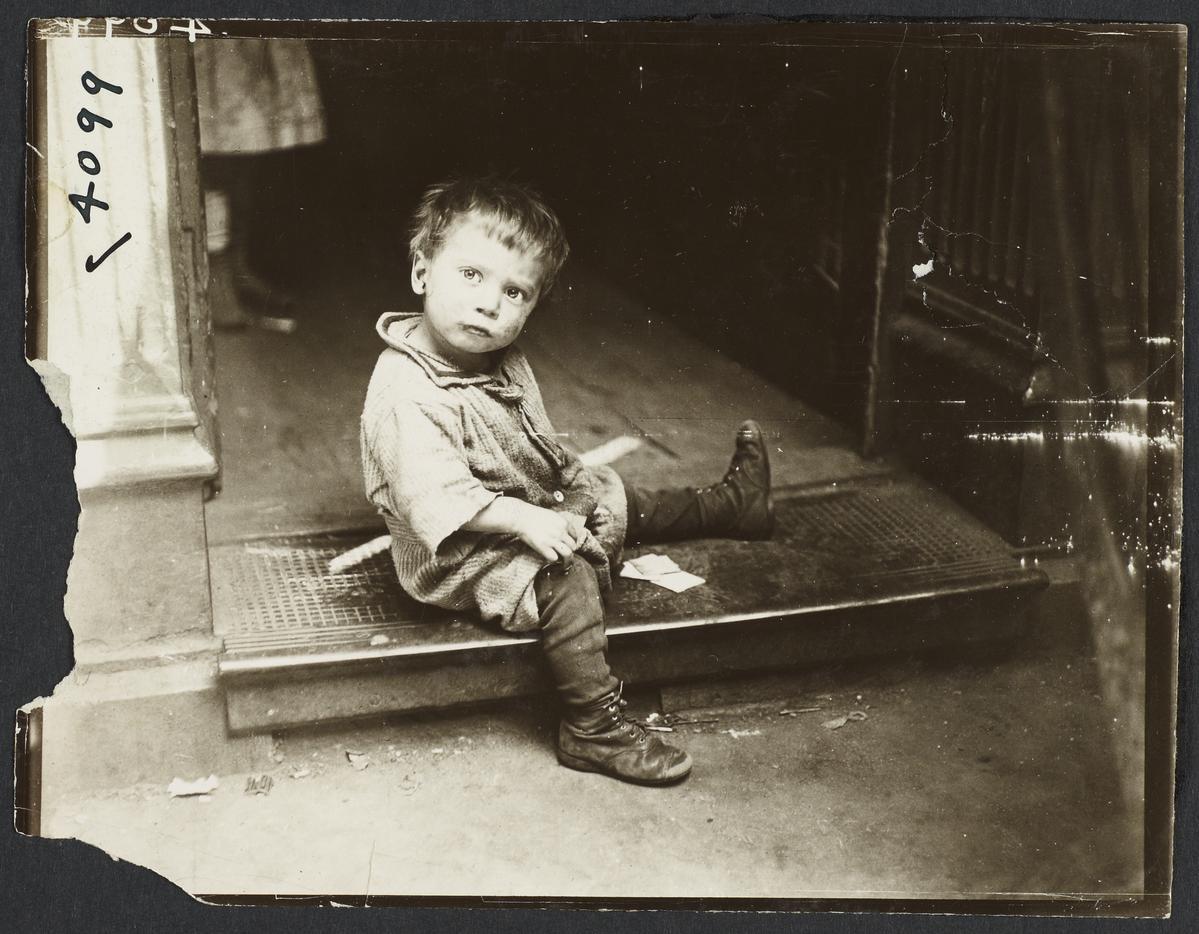 Boy Sitting on Grate