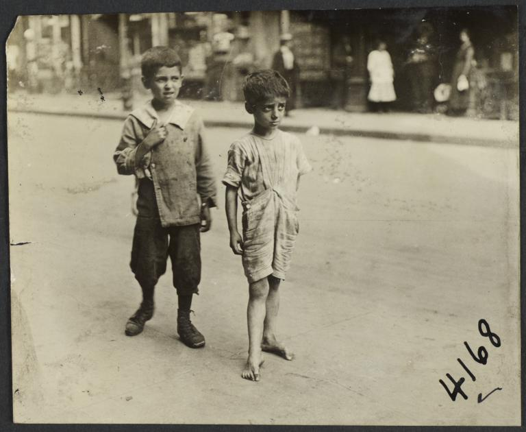 Barefoot Boy and Boy in Shoes on Sidewalk