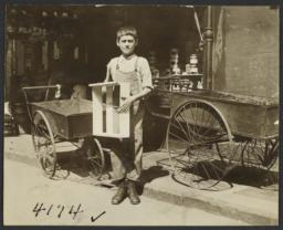 Boy with Box near Empty Pushcarts