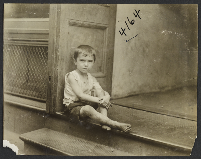Boy Sitting at Entrance to Building