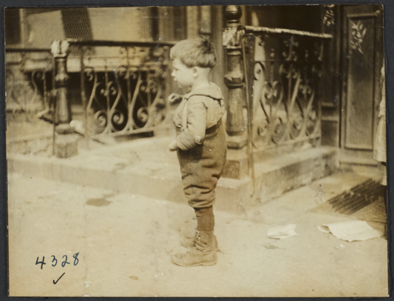 Boy Standing near Wrought Iron Railings