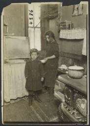 Two Children in Kitchen with Birdcage