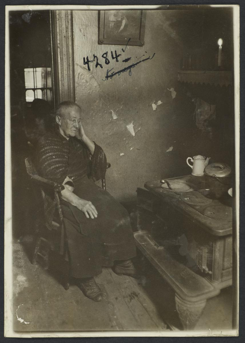 Old Woman in Chair near Stove