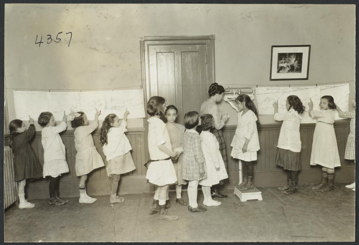 Mulberry Health Center Album -- Girls Pointing to Weight on Charts