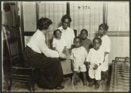 Columbus Hill Health Center Album -- Woman and Four Children with Nurse
