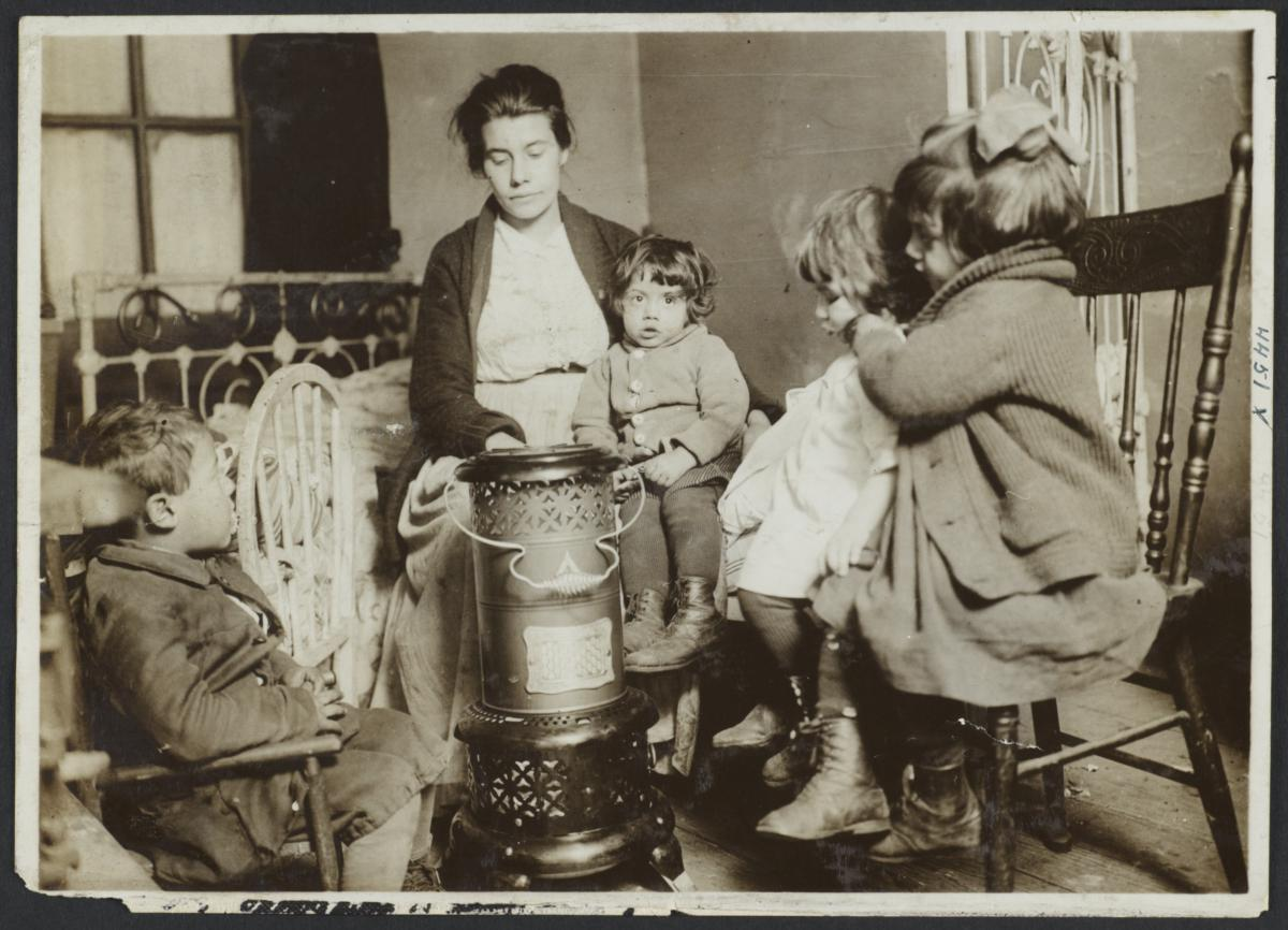 Woman  with Four Children Around Heater