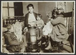 Woman  with Four Children Around Heater