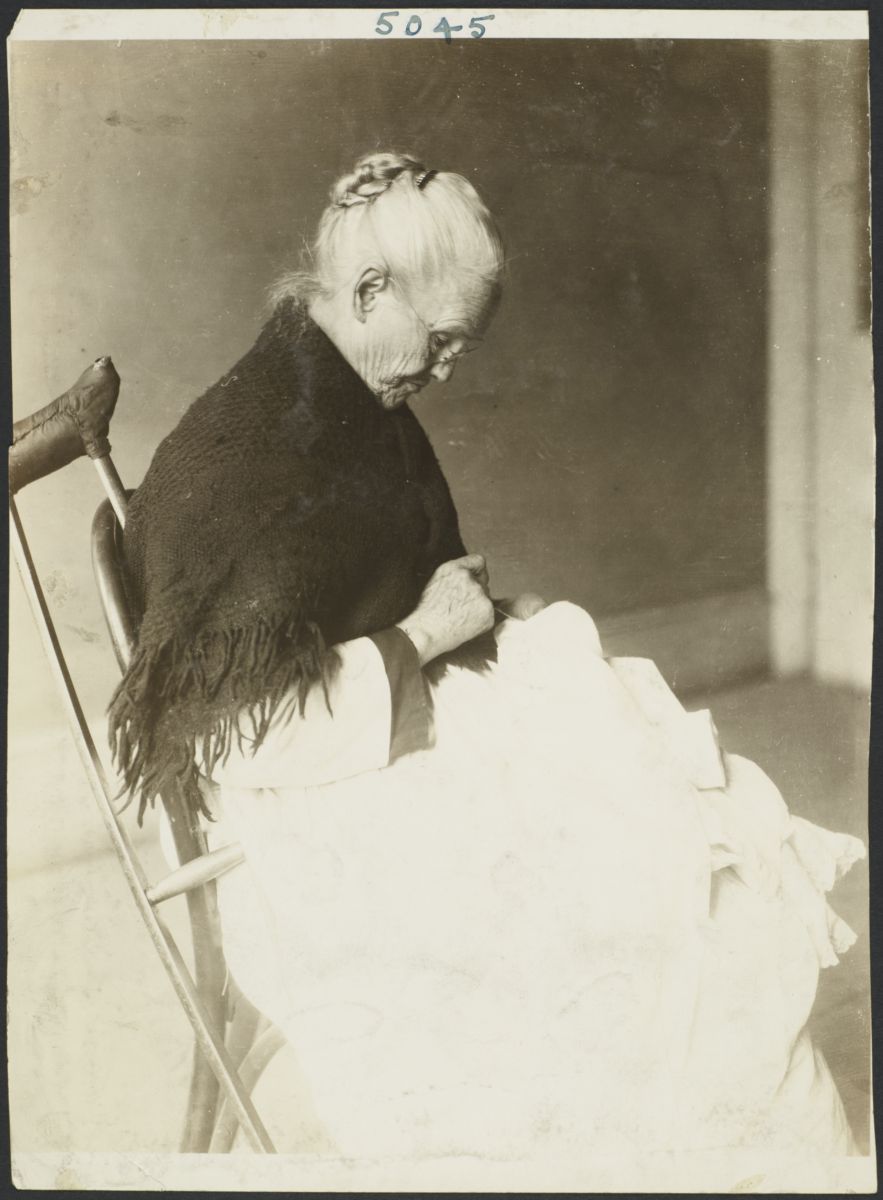 Women's Work Rooms Album -- Old Woman with Crutch Sewing