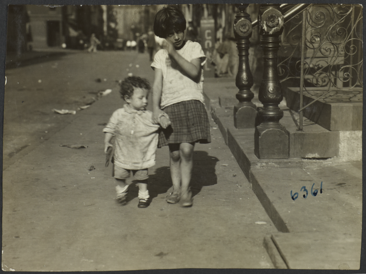 Girl Holding Hand of Small Child on Sidewalk
