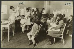 Columbus Hill Health Center Album -- Woman Teaching Mothers about Clothing