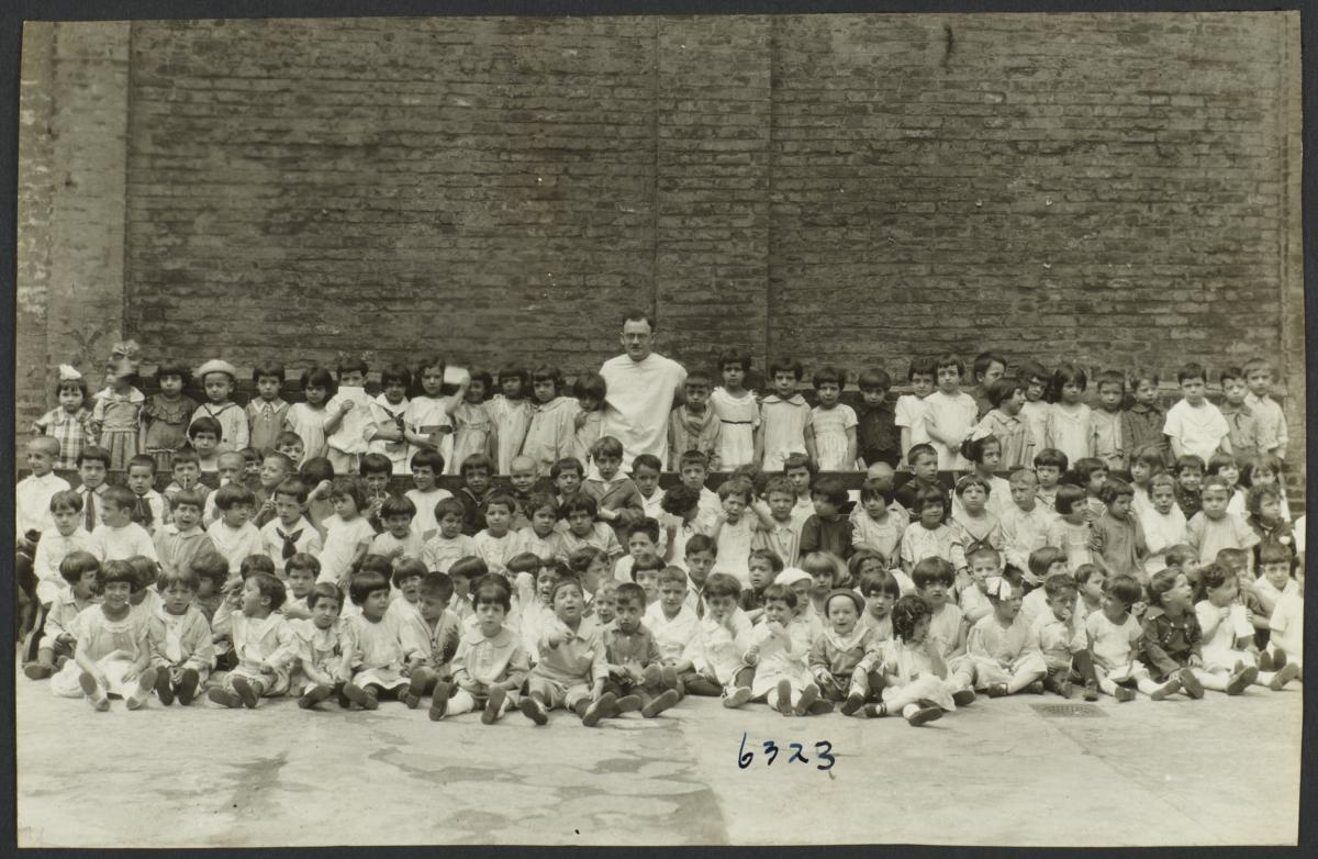 Mulberry Health Center Album -- Man with Large Group of Children