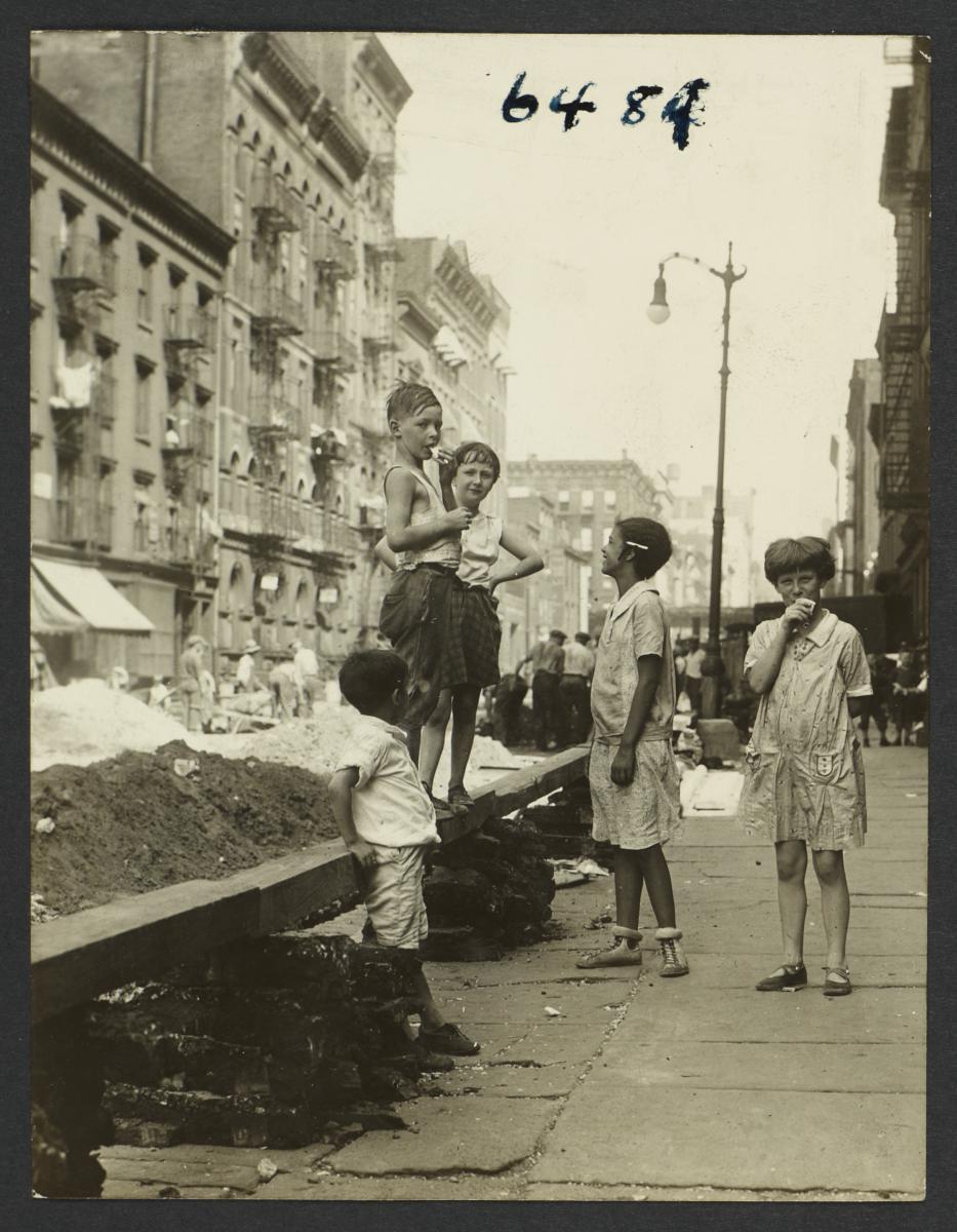 Children on Sidewalk near Mounds of Dirt