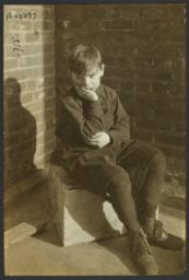 Boy Sitting on Crate