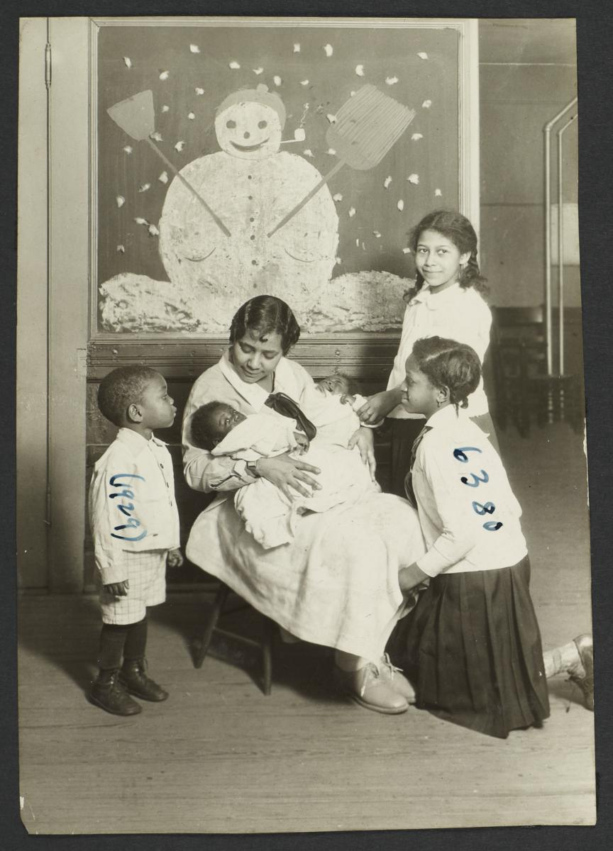 Columbus Hill Health Center Album -- Nurse with Children in front of Snowman Painting