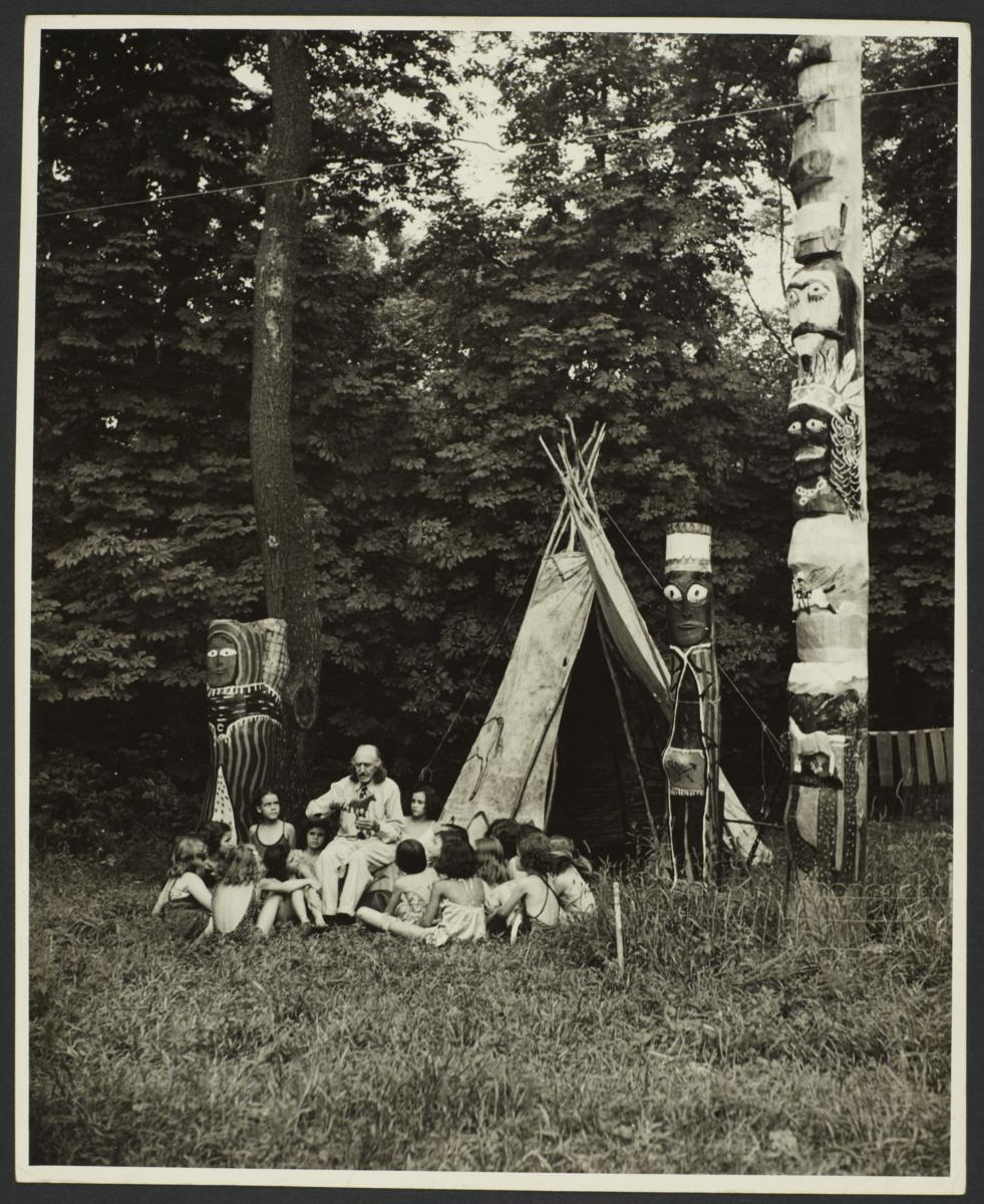 """""""Bronco"""" Charlie with Group of Children near Teepee and Totem Poles"""