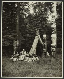 """Bronco"" Charlie with Group of Children near Teepee and Totem Poles"