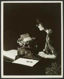 Woman at Typewriter in Dark Room