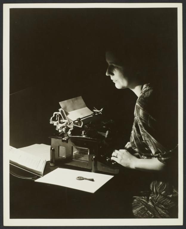 Woman at Typewriter in Dark Room