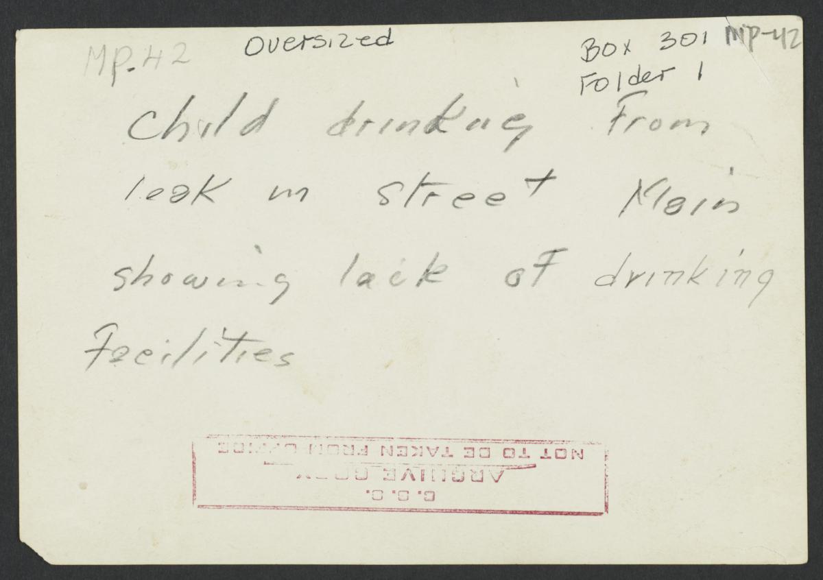 Child Drinking From Leak in Street Main