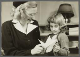 "Nurses' Educational ""Keep Well"" Series Album -- Nurse Showing Paper Bird to Girl"