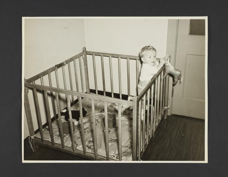 Picturing Some of the Principles of Child Care Album -- Baby Standing Up in Playpen