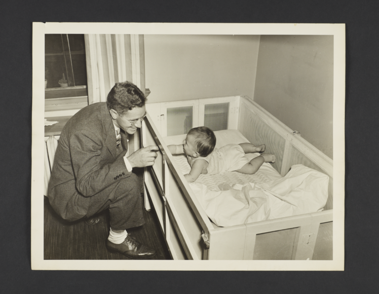Picturing Some of the Principles of Child Care Album -- Father Plays With Baby in Crib