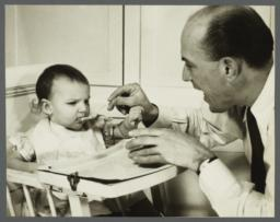 Lenox Hill, 1948-1949 Album -- Man Feeding Baby