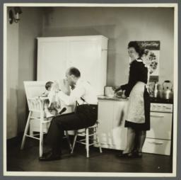 Lenox Hill, 1948-1949 Album -- Man Playing with Baby in High Chair