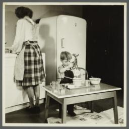 Lenox Hill, 1948-1949 Album -- Woman with Boy in Kitchen