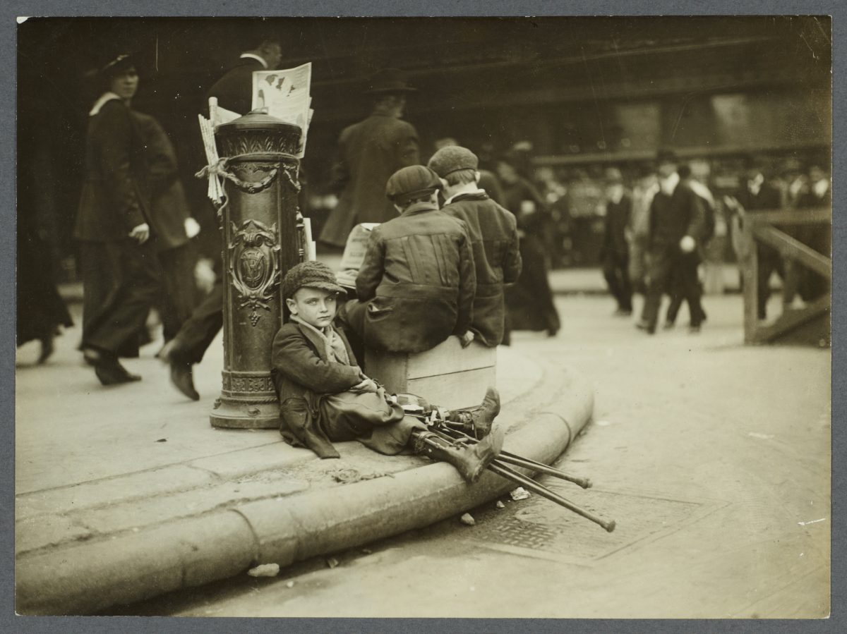 Crippled Boy Resting Against Fire Alarm
