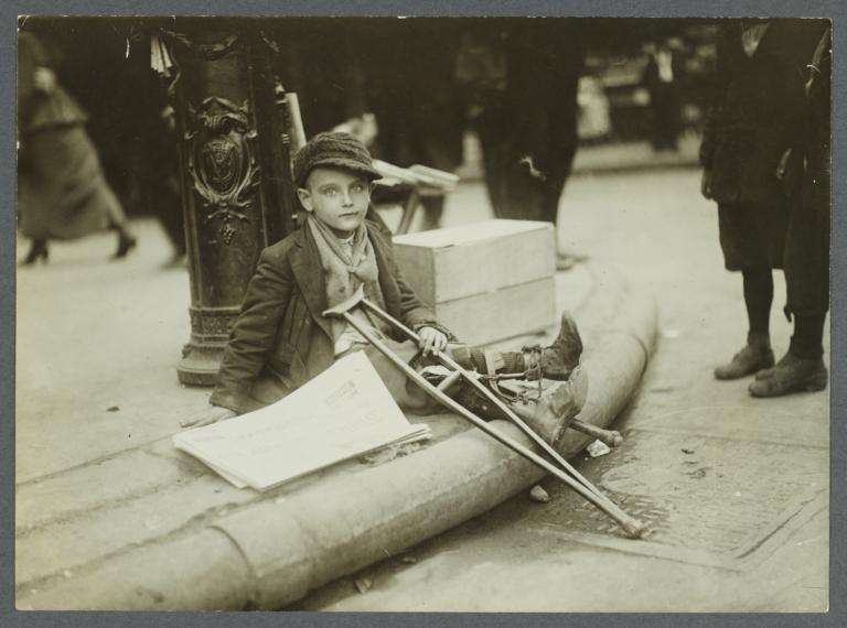 Boy with Crutches Resting Against Fire Alarm