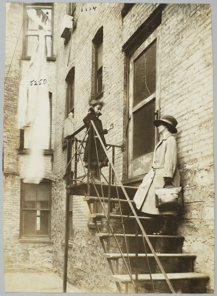 Mulberry Health Center Album -- Visiting Nurse on Tenement Back Stairs